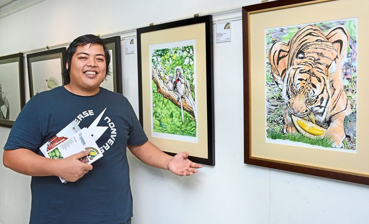 Nasir Nadzri, 31 - a tubby man with a round face and wispy black hair. He is pictured smiling open-mouthed while gesturing towards his painting of a tiger eating durian. He is holding exhibition brochures.
