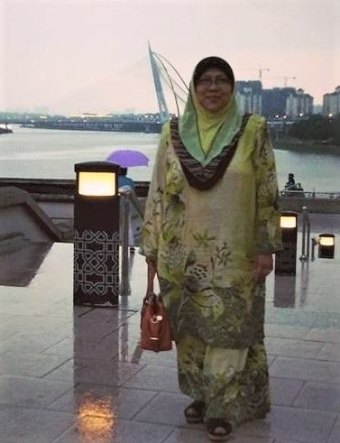 Normah Mohd Yusoff wears ruffled headscarf and baju kurung and carries a handbag. She poses in front of a lake. She has a round face and high cheek bones.