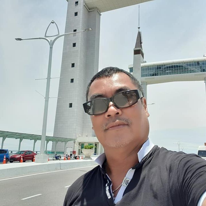 Alan Koh Chong Beng takes a selfie at a bridge in Terengganu. He wears sunglasses.