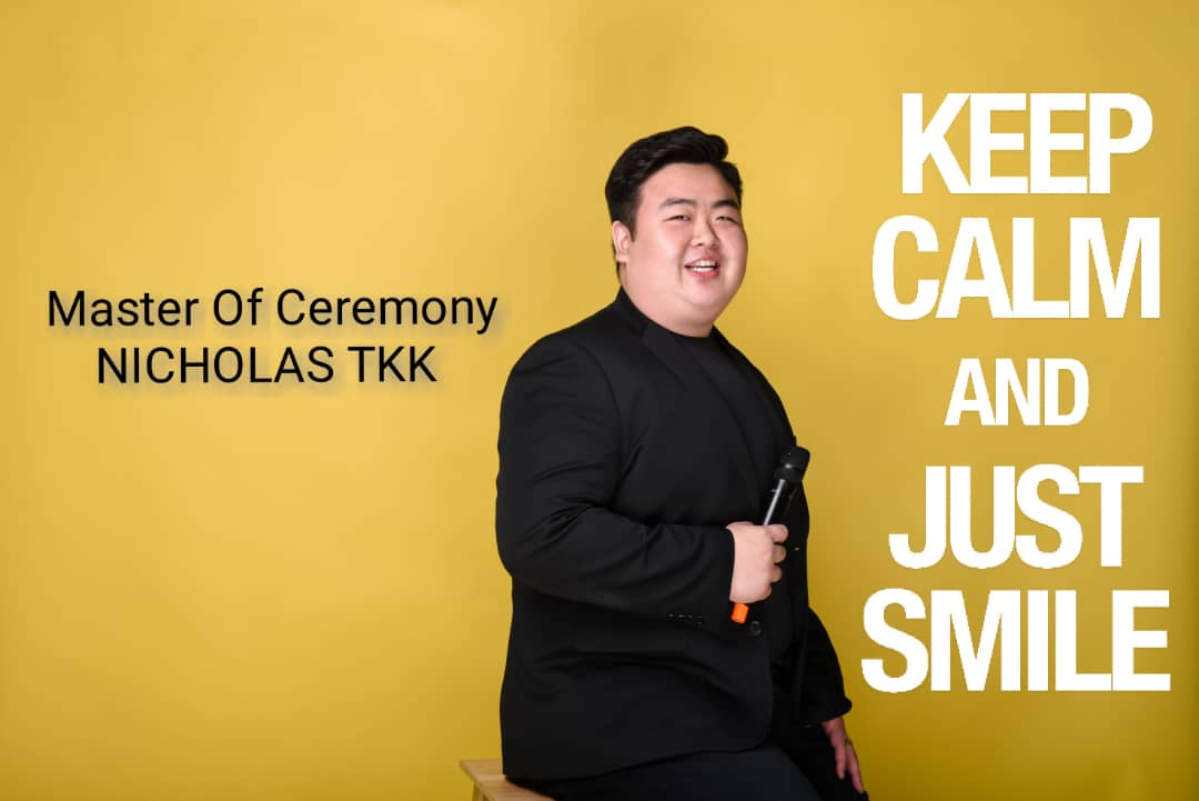 Poster for Nicholas TKK as master of ceremony. He is smiling, dressed in all black and holding a microphone. The poster states: 'Keep calm and just smile'.