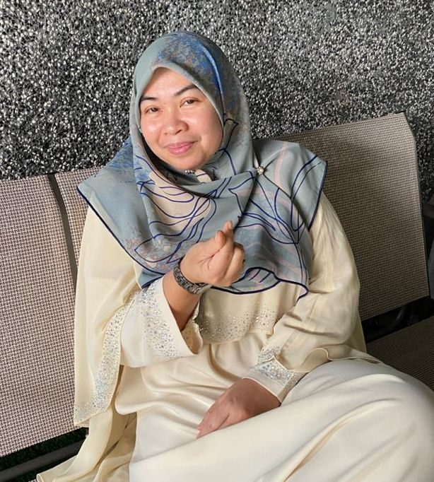 Rahimah dressed in white, poses with a smile while making a heart shape with her fingers