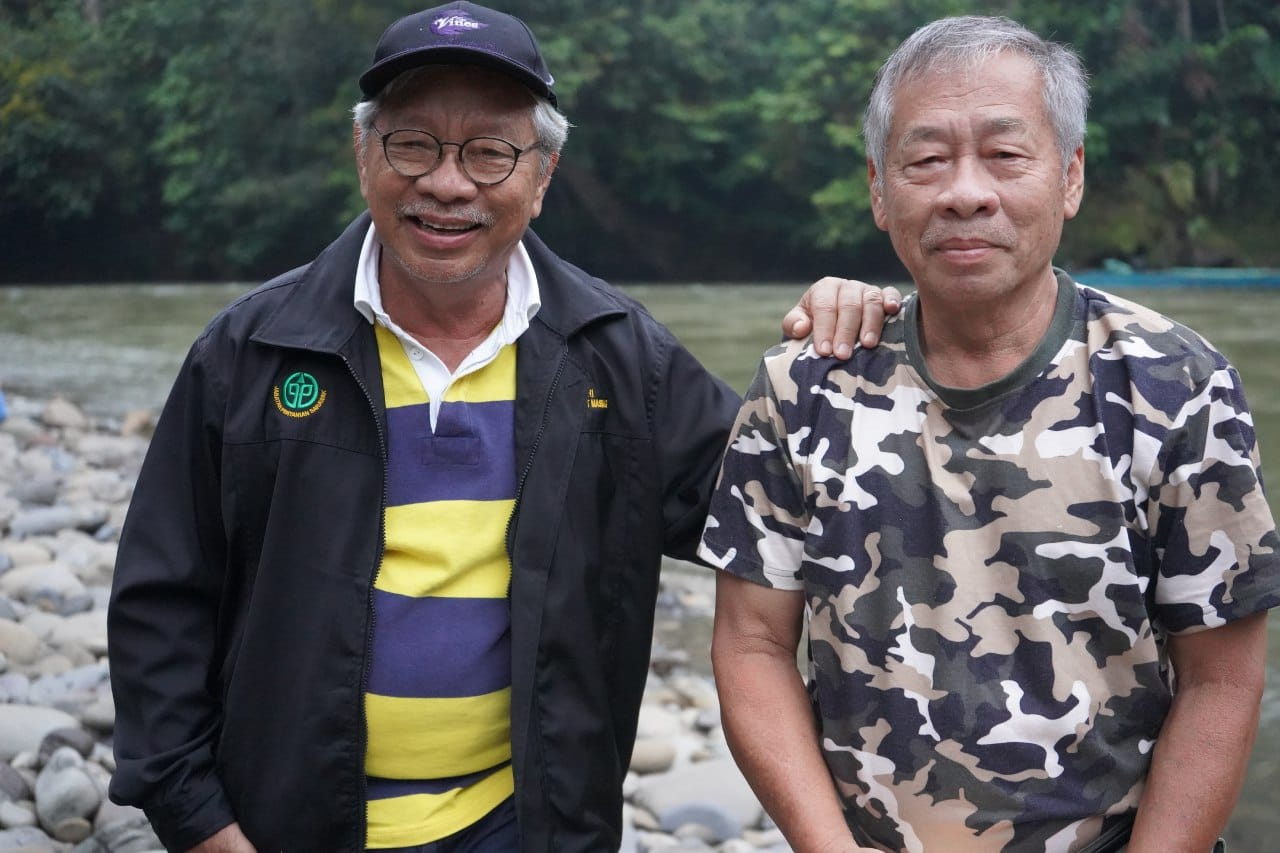 James and Jantai Masing stand on a river bank. Elderly men with grey hair. James, left, has dark-rimmed glasses and a hand on Jantai's shoulder. Jantai is in a T-shirt with army fatigue print.