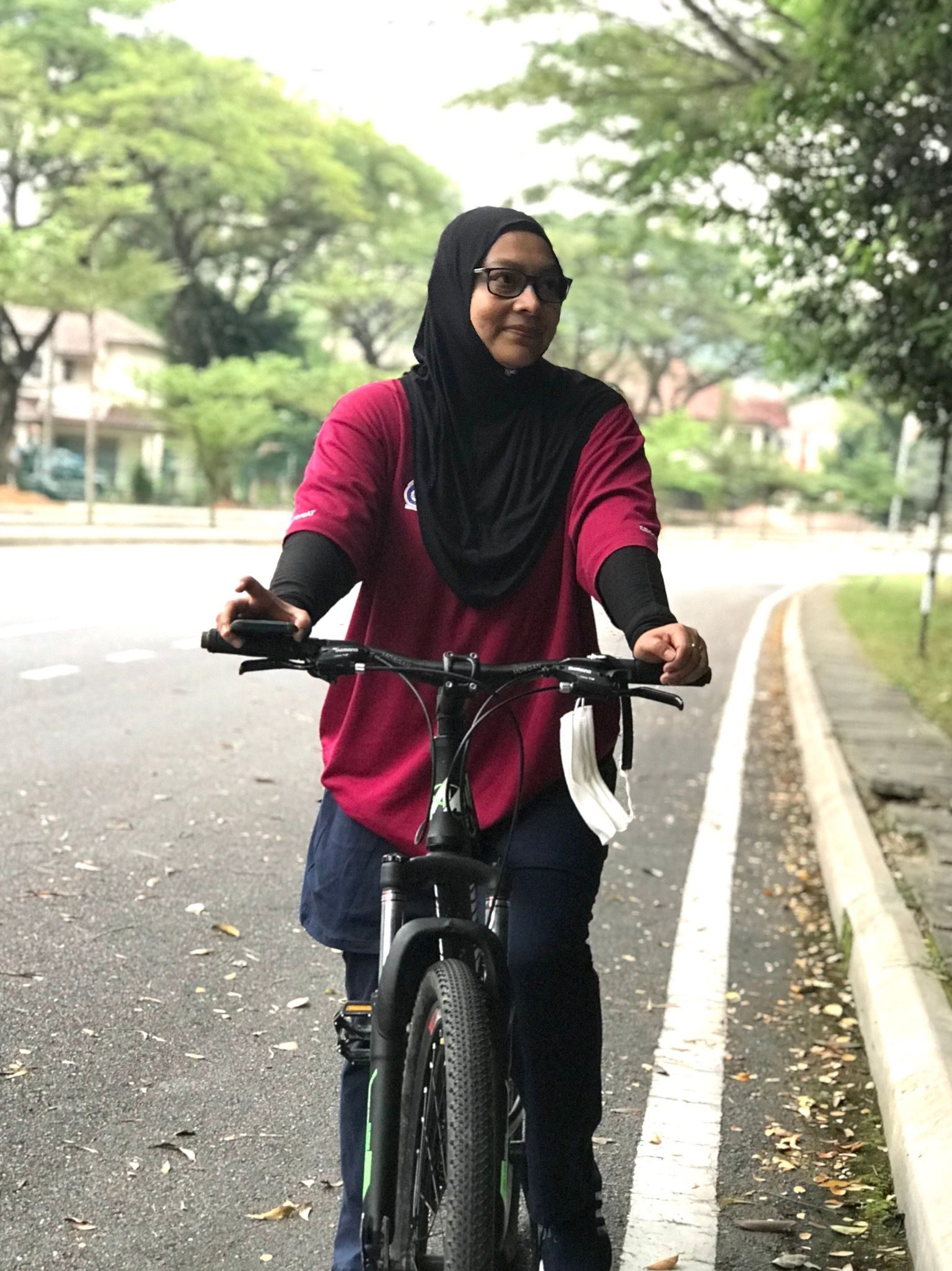 Zainun binti Mohamed Rani rides a bicycle. She is in a black headscarf, red T shirt and dark-rimmed glasses.