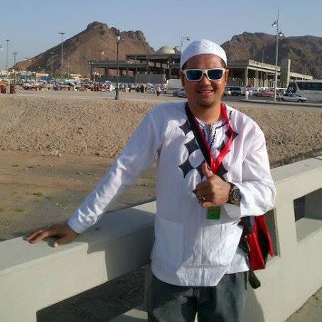 Faizal Chik, wears a white kopiah, white kurti, sunglasses and a sling bag.