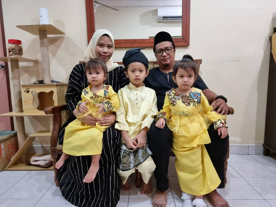 Anual Ridzuan Mustafa, 38, sits next to his wife. Their three children are in front of them, one daughter is on his lap.