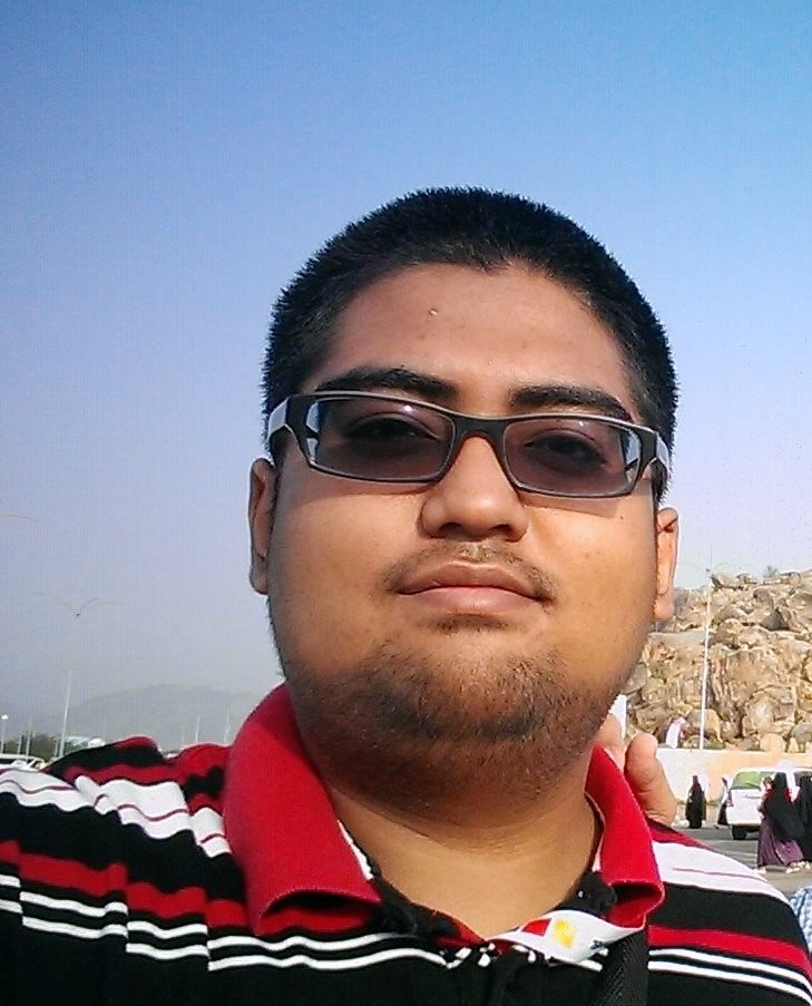 Ahmad Faid bin Ahamad Norwawi. A stocky man in short hair, stubbled goatee and sunglasses, wearing a striped collared T-shirt.