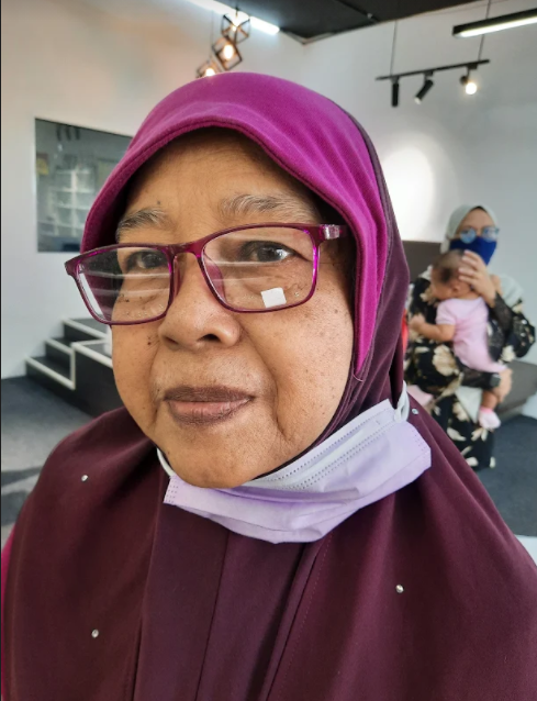 Khamshah Binti Ismail in a picture from March 2021. She is wearing glasses with purple frames, matching her headscarf.
