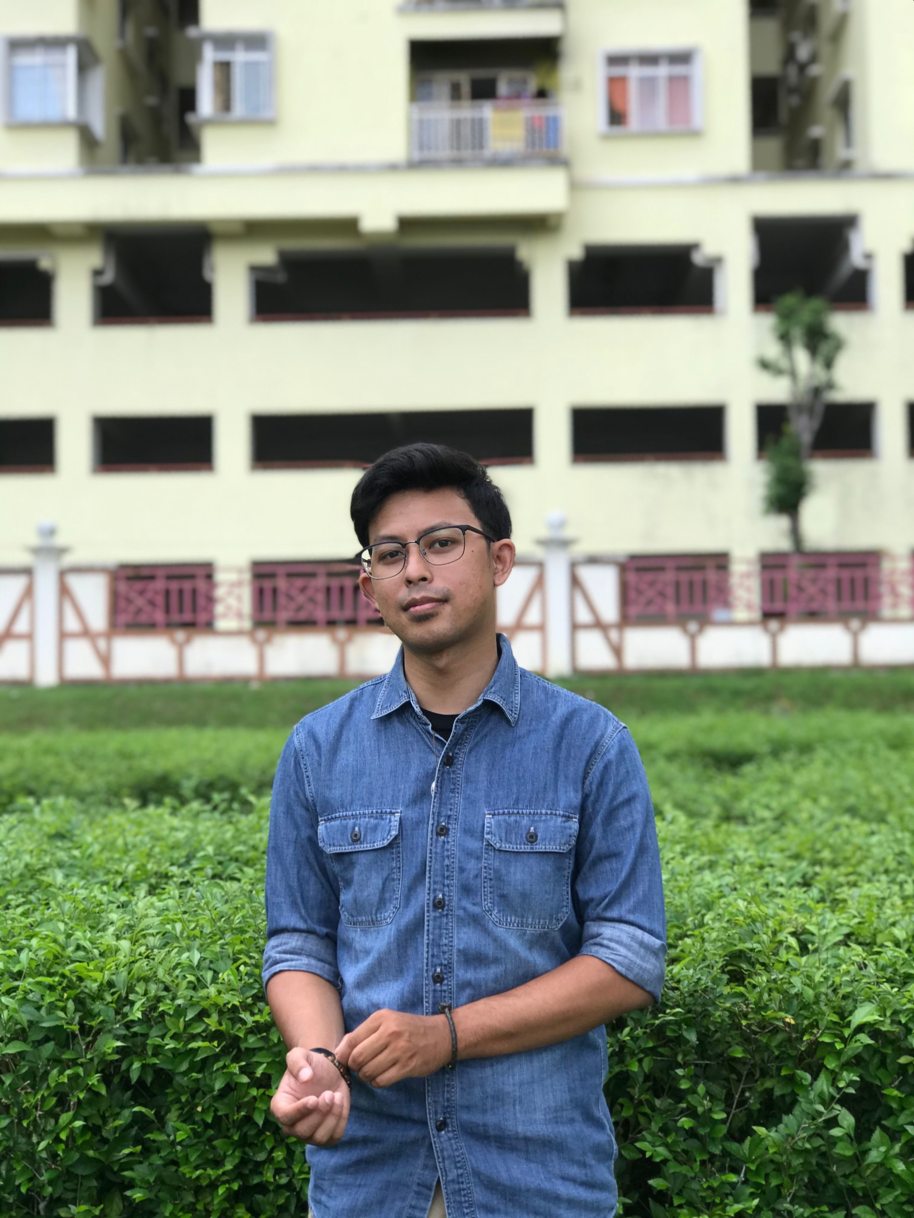 Mohammad Shahirul Azwan Bin Mansor is a young man. He stands in front of some shrubbery, wearing a denim shirt and glasses.