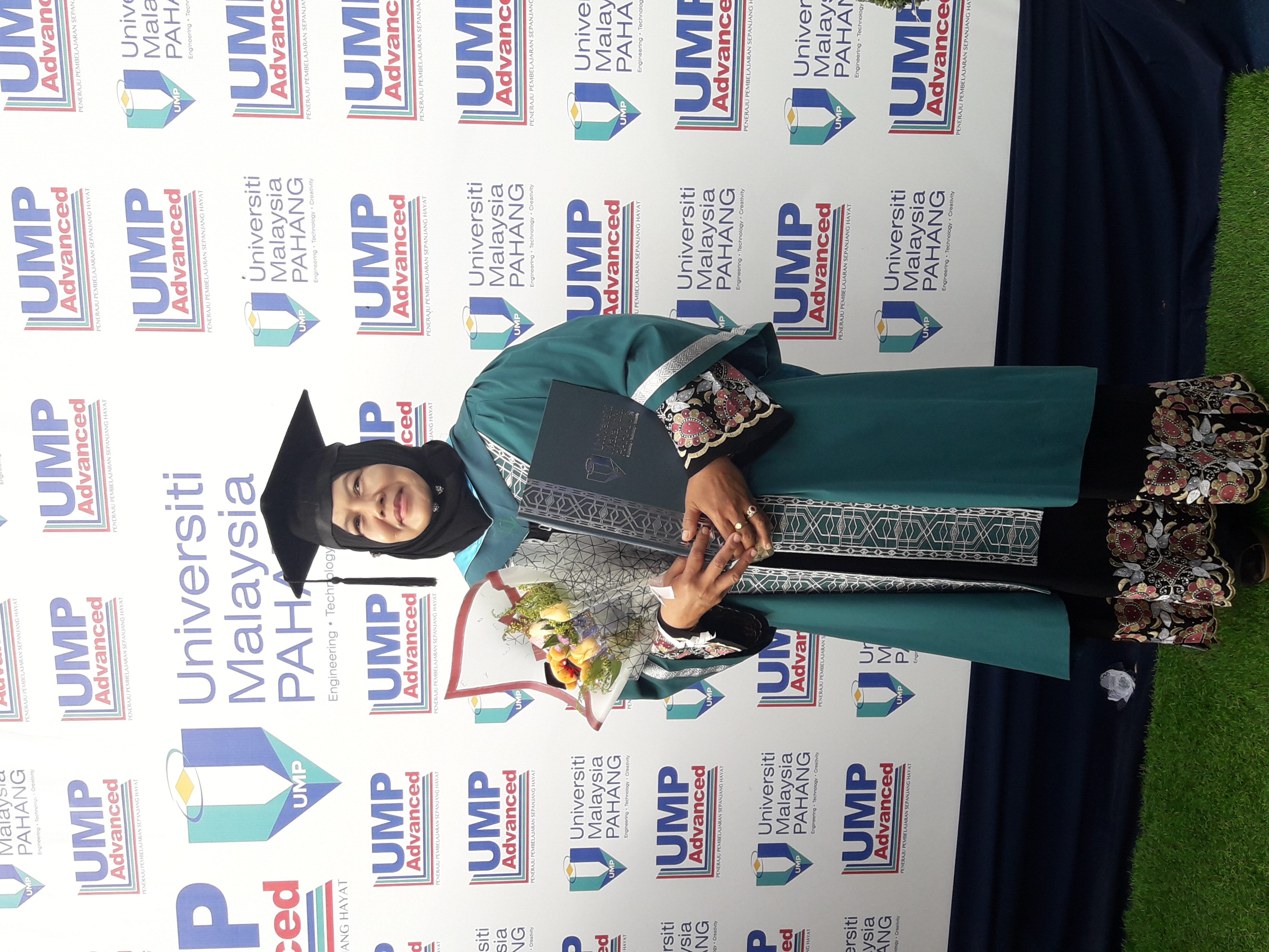 Noorlizah donned in her graduation attire, holding a bouquet of flowers and a degree
