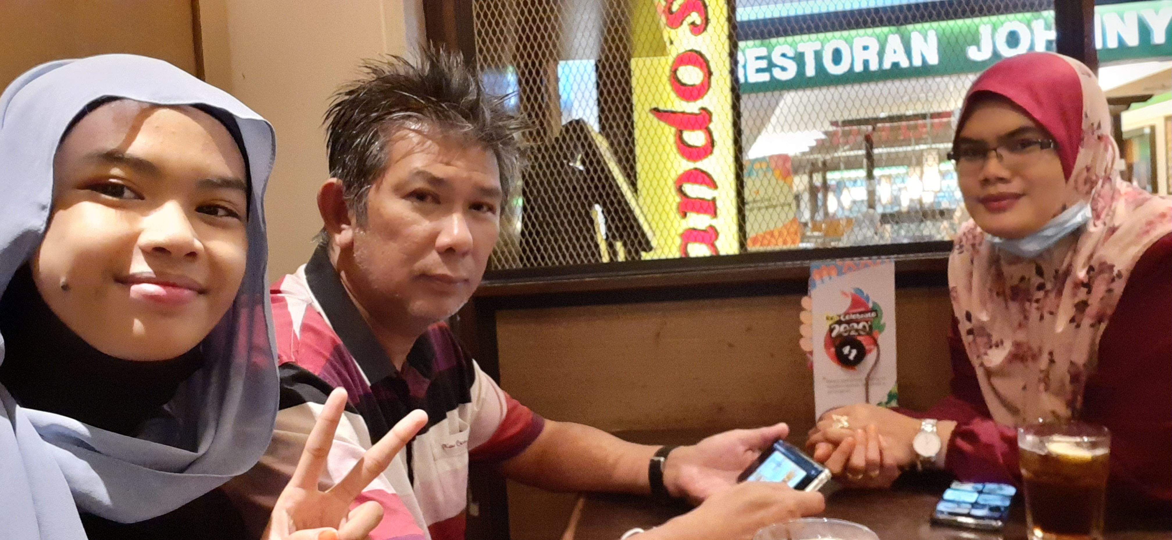 Kamaruzaman bin Hassan shares a meal with his family at Nando's. He has greying hair and a youthful face.