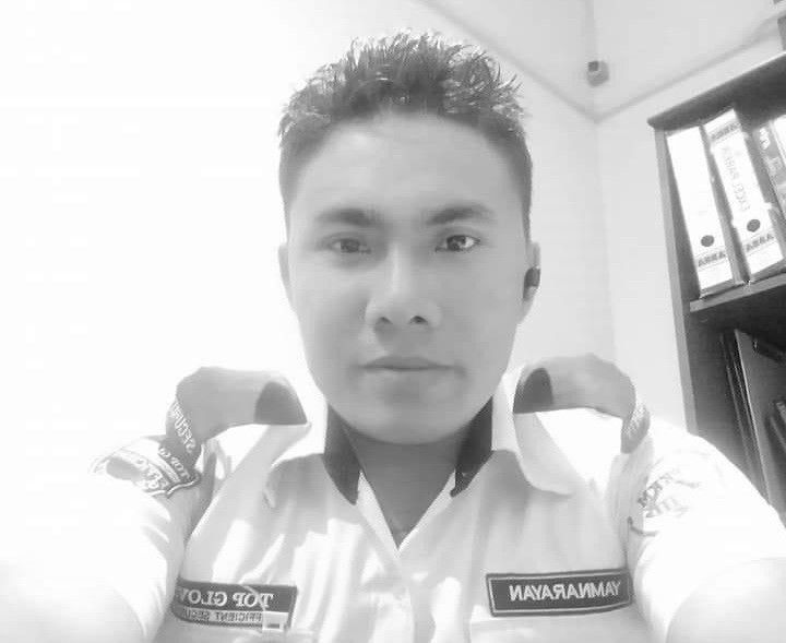 Yamnarayanan Chaudury Tharu 29 takes a selfie while wearing his security guard uniform, in an office. He is also wearing a communication device in one ear. He has spiky, gelled hair and is fair-skinned.