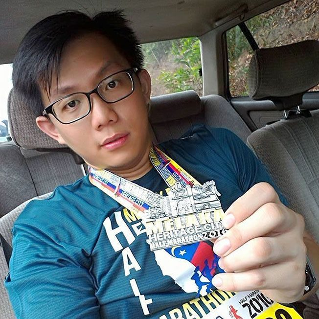 Soo Eng Kuan, a bestacled young man with brush-like hair, showing his Melaka Heritage City half marathon 2016 medal.