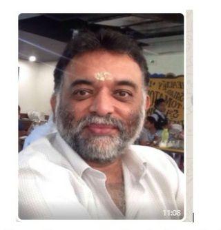 Dhineshnarayanan, 52, has a grey beard and dark hair. He is wearing a white collared shirt.