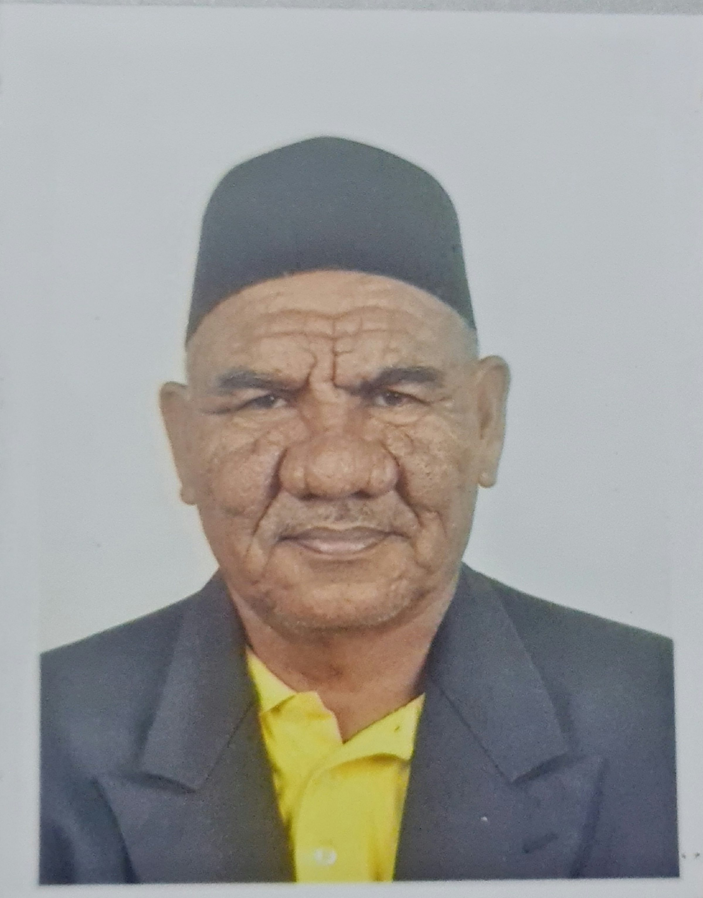 Passport image of Jalaluddin Bin Mohd Jamin. He is wearing songkok and a blazer. He has a wrinkled face, bushy eyebrows and a bulbous nose. He is smiling slightly.