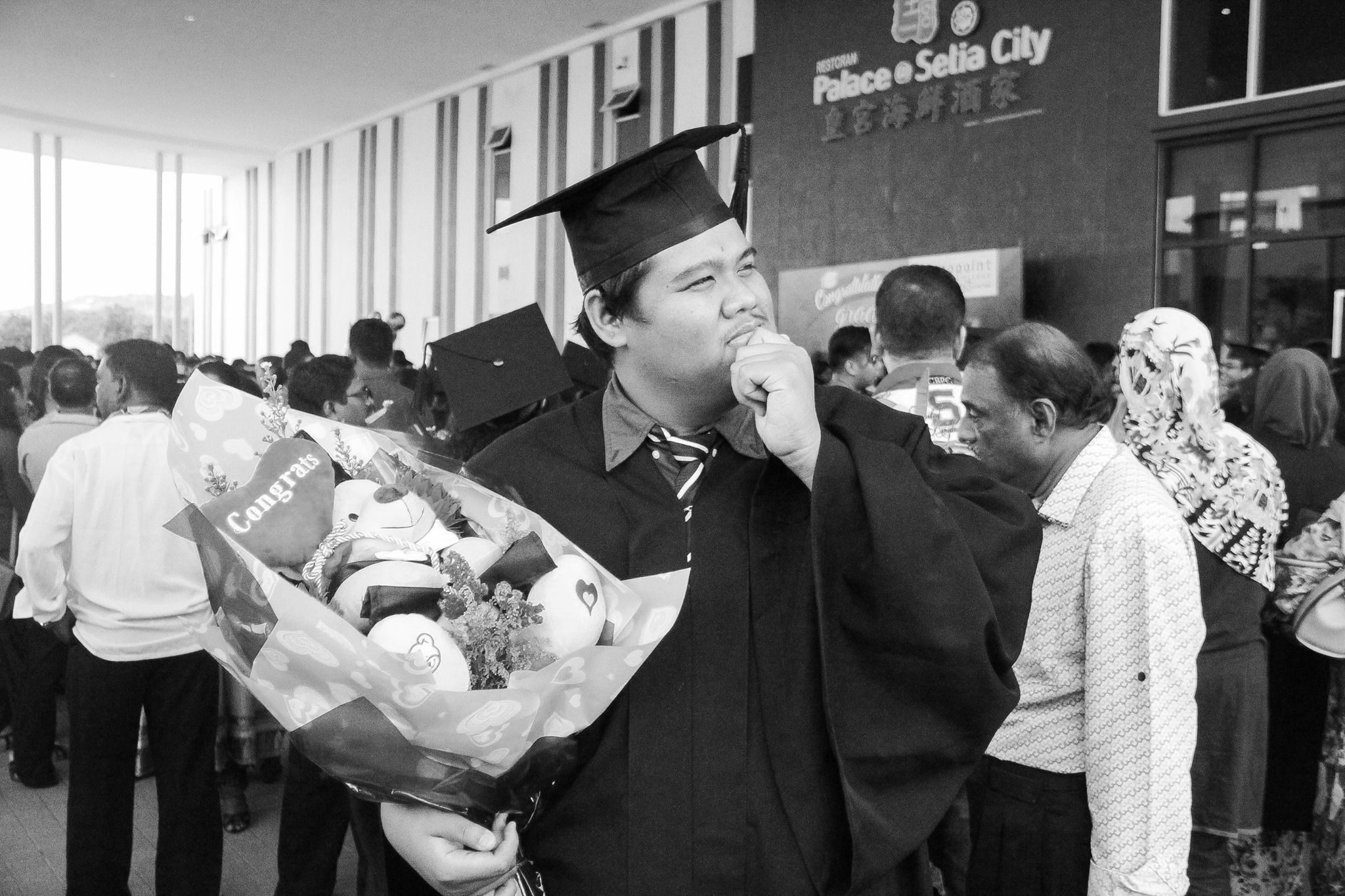 Muhammad Hilman Bin Mohd Hardi on his graduation day, in a cap and gown and holding a teddy bear bouquet.
