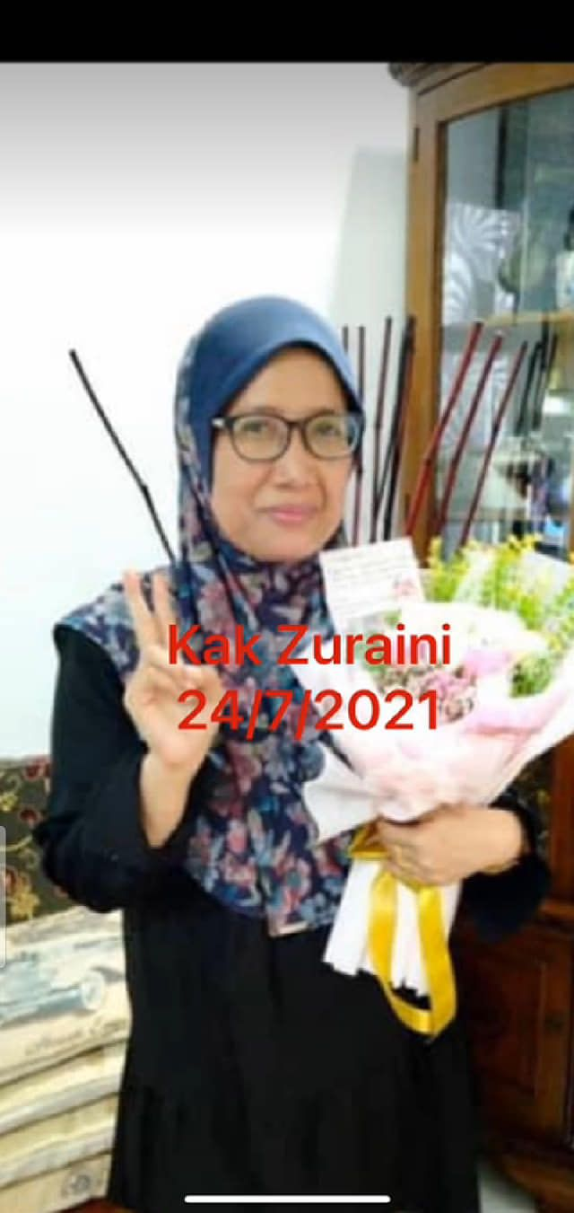 Zuraini Paiman holding a bouquet of flowers. She is wearing a headscarf and is showing the peace sign. The photo is captioned 'Kak Zuraini 24/7/2021'
