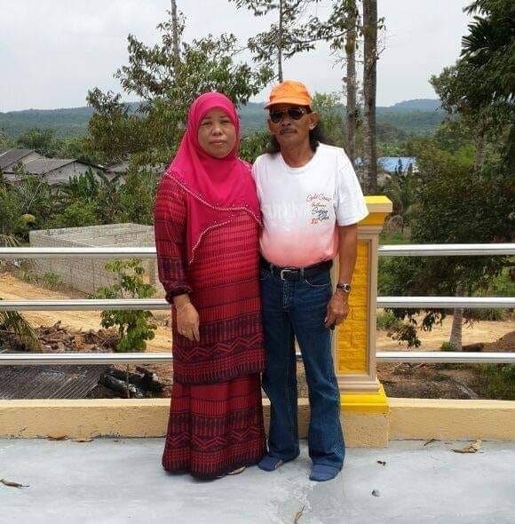 Esah Jaafar with her husband. She was a middle-aged woman and was dressed in a headscarft and baju kurung.