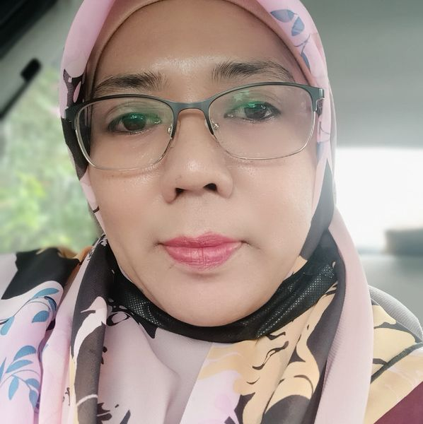 Maheran Marzuki takes a selfie in her car. She wears spectacles and and a headscarf.