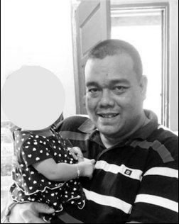 Ahmad Zazlan Mohamed Ghazali carrying a toddler. The toddler's face is not shown.