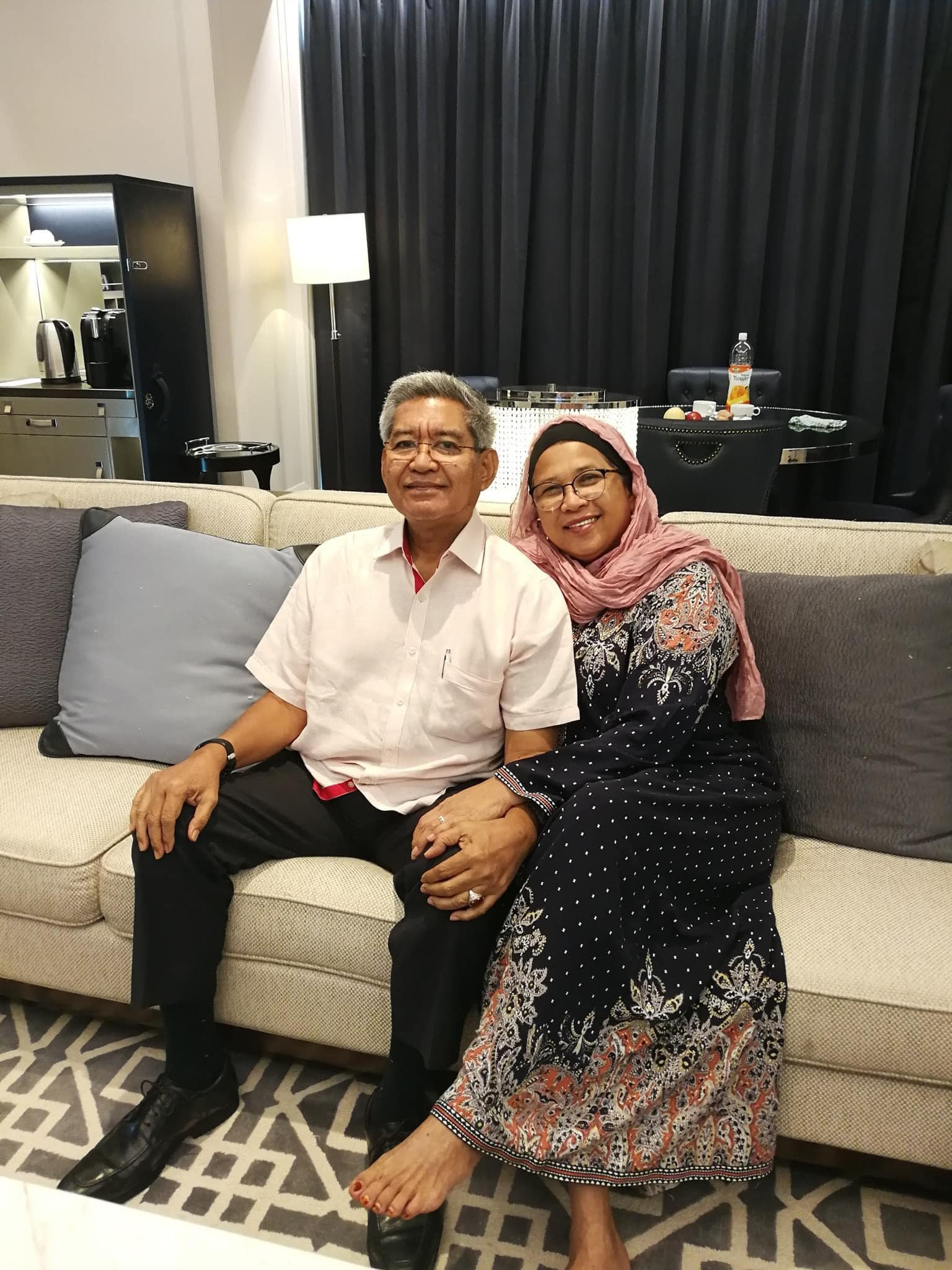 Aziz M Yusof and his wife sit on a sofa. She has her hand on his lap. They are smiling. Aziz has grey hair and wears rimless glasses.
