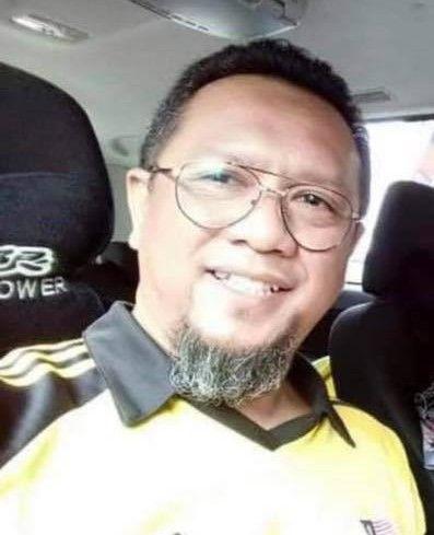 Mohd Dizal Ramelan smiles in a selfie. He wears wire framed glasses and sports a graying goatee. He is wearing a Harimau Malayajersey.