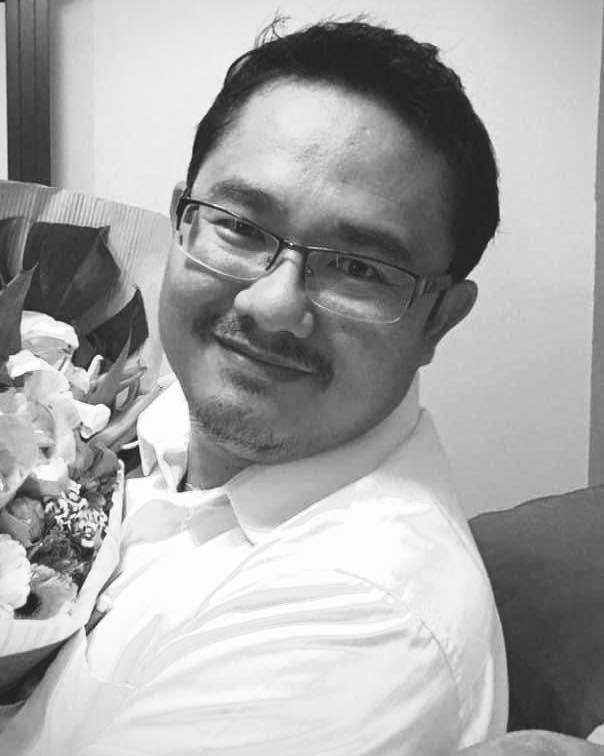Bespectacled Ahmad Redzuan Bin Md Tahir in a white shirt, smiling. He is holding a bouquet of flowers.