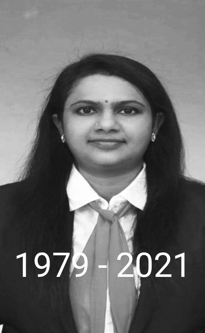 Indra Nadarajan in a passport photo. She has long hair and is wearing a shirt and blazer, earrings, a nose ring and a pottu on her forehead.