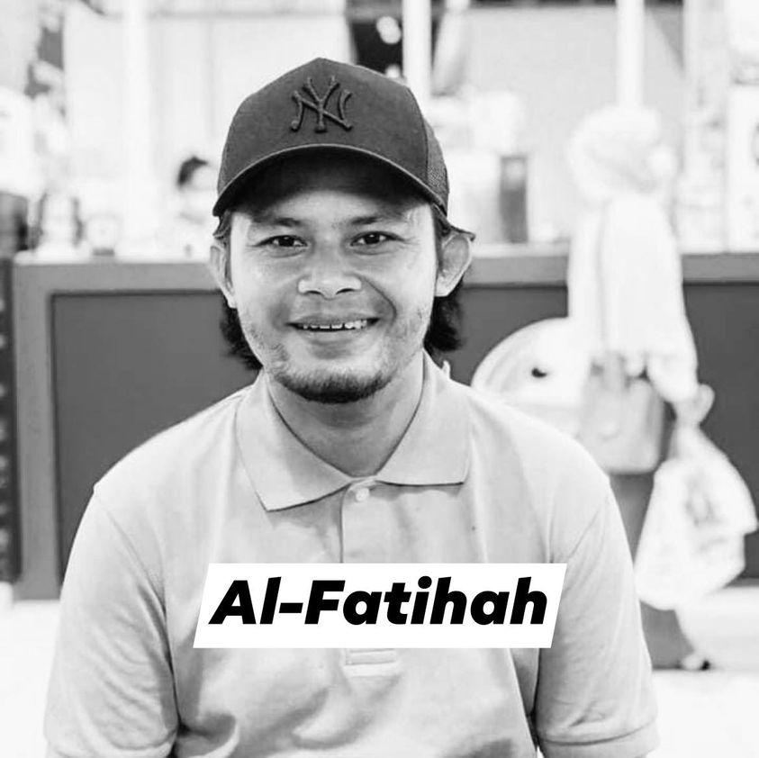 Mohd Rozi Jaafar smiles for the camera. He is wearing a collared T-shirt, buttoned to the top and a New York Yankee baseball cap. He has hair down to his collar and a goatee.
