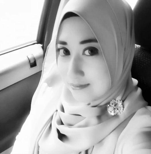 Nur Hanani takes a selfie in a car. she wears a headscarf and a brooch.