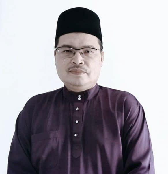 Anuar Mat Esa strikes a serious pose in baju melayu and songkok.