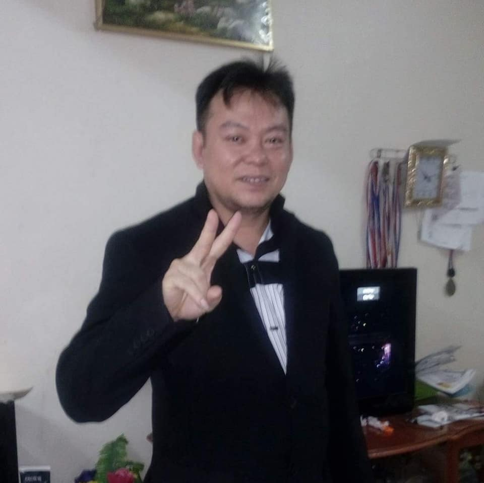 Enriti Engkang shows the peace sign and smiles as he poses at home. In the background are medals.