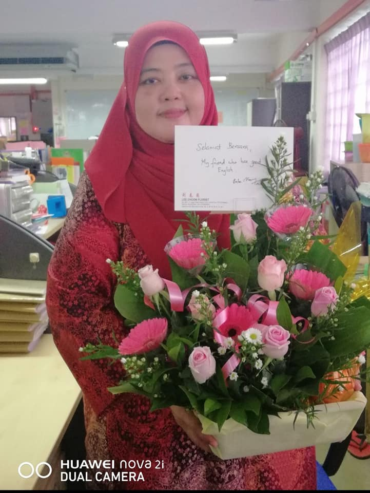 Zarinah Rahmat with a bouquet of flowers she received on her retirement