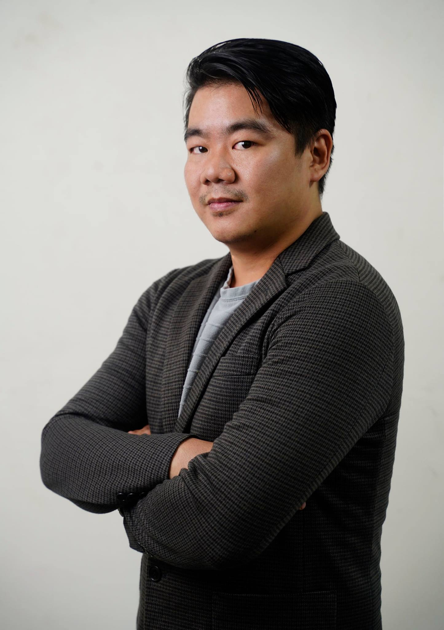 Professional portait of Chong Hai Liang in a black jacket, arms crossed.