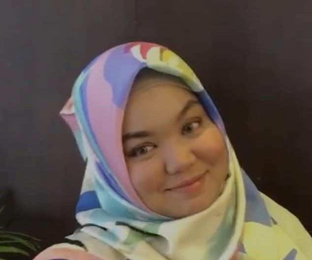 Herni Yusnilah dons a colourful headscarf and smiles for the camera.