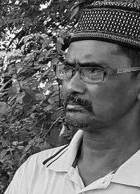 Azizan Abdul Rahman - wears spectacles, a kopiah and a collared T-shirt. He has a mustache.