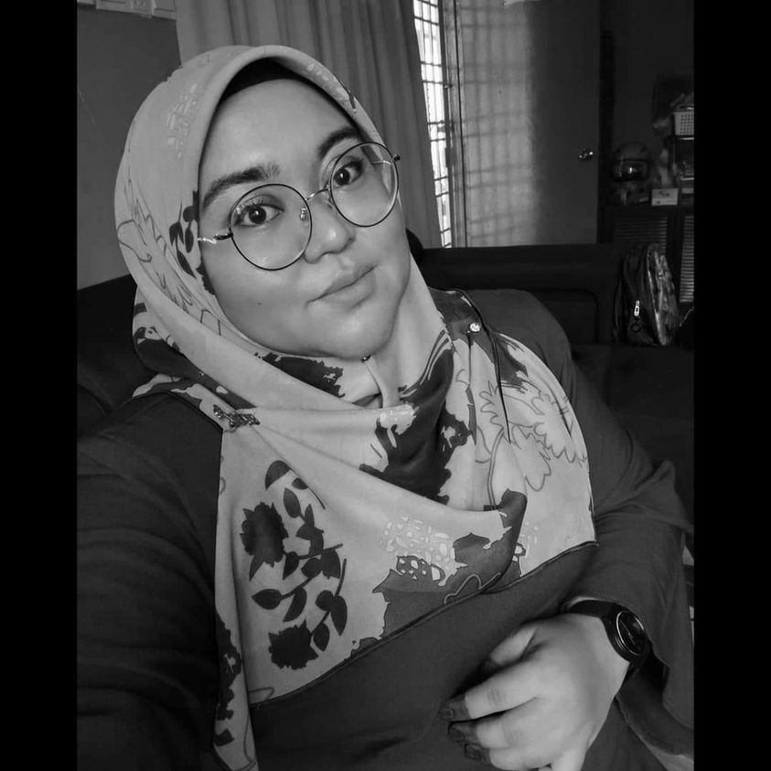 Noorzubaidi Matlazim poses for a selfie. She wears large round framed glasses and a floral headscarf. Her fingers ae decorated with henna.