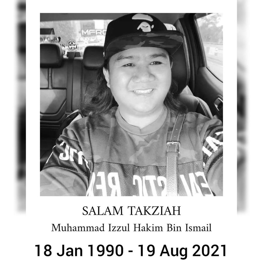 Muhammad Izzul Hakim Bin Ismail, 18 Jan 1990 to 19 Aug 2021. The man has a round face, long hair and an easy smile. He wears  cap and a jersey and is sat in his car.