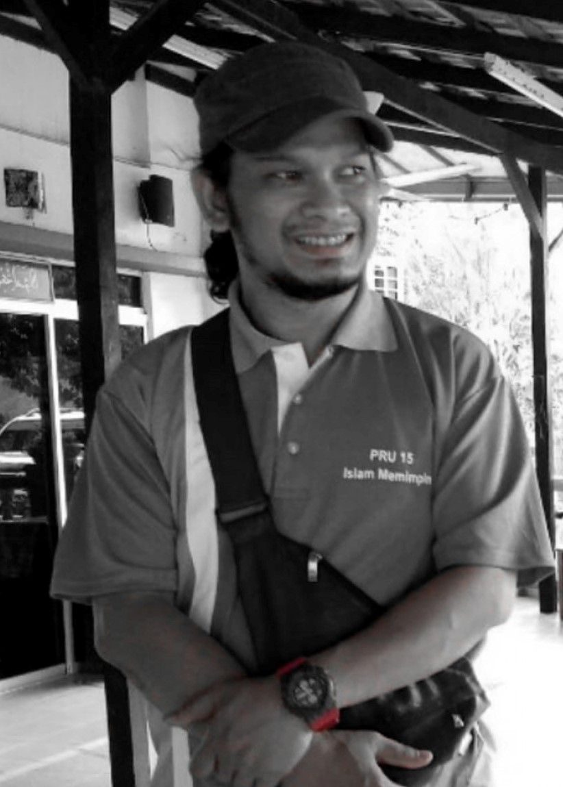 Suhairul Afzan Supian, a man witha goatee. He is smiling, wears a cap, collared T-shirt and a waist pouch.