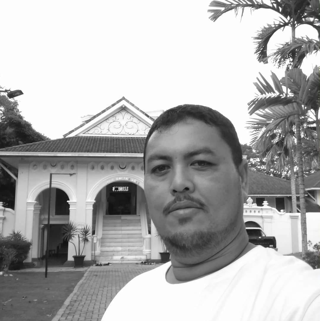 Bukhori posing in front of a large house