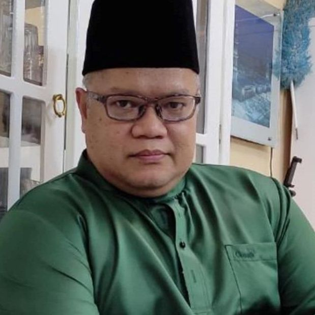 Muhd Ikmal Deling Abdullah @ Deling Gaong, middle aged, stocky and bespectacled man, dressed in baju melayu and songkok.
