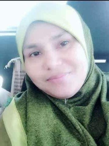 Noranisah binti Ramli aka Umie smiles slightly. She is wearing a green headscarf.