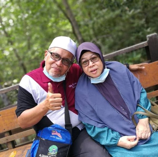Ab Razak Md Yusoff shows the thumbs up to the camera. He is wearing a white kopiah and has a grey goatee. He poses with his wife.