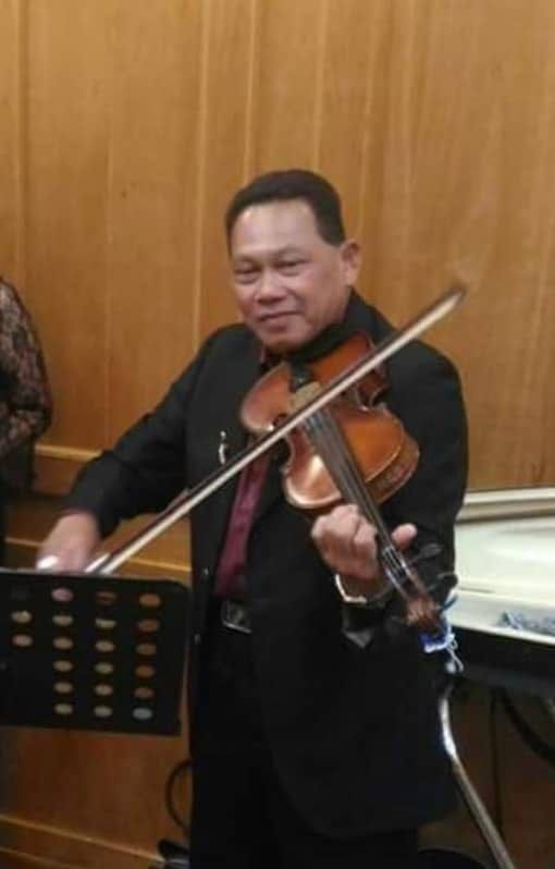 Hashim Arifin plays the violin. He wears a black suit and maroon shirt.
