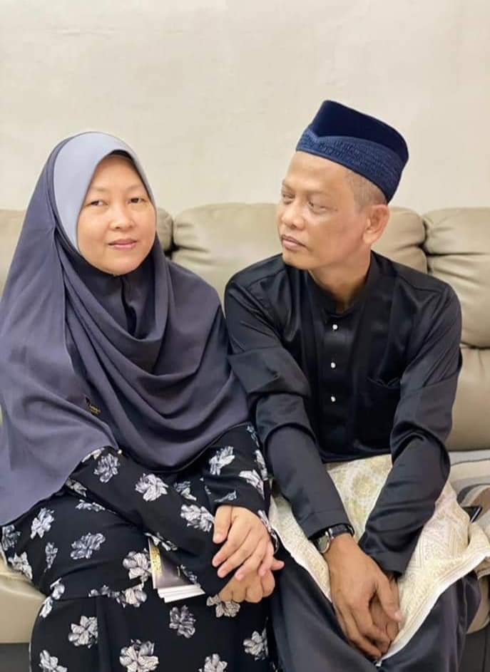 Zaleha Kamiran with her husband. They are wearing matching black outfits. She wears a grey headscarf and he wears a songkok.