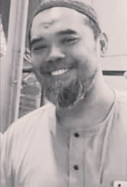 Sharudin Mohd Rafiee smiles. He has a greying beard and is wearing a kopiah and jubah.
