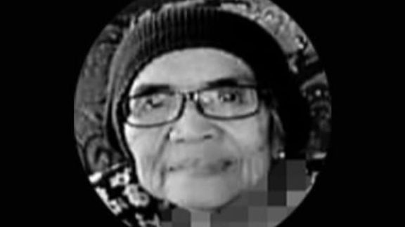 Che Esah Che Kob wears dark rimmed glasses and a serkup to cover her hair. She smiles slightly.