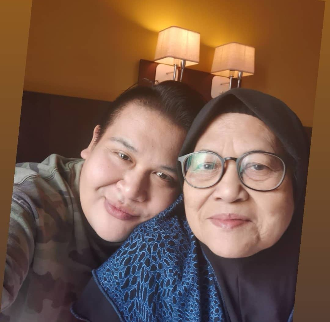 Aishah Abdul Aziz with her son Syarizzuan, who is leaning his face on her shoulder. Aishah is wearing a headscarf and dark rimmed glasses.