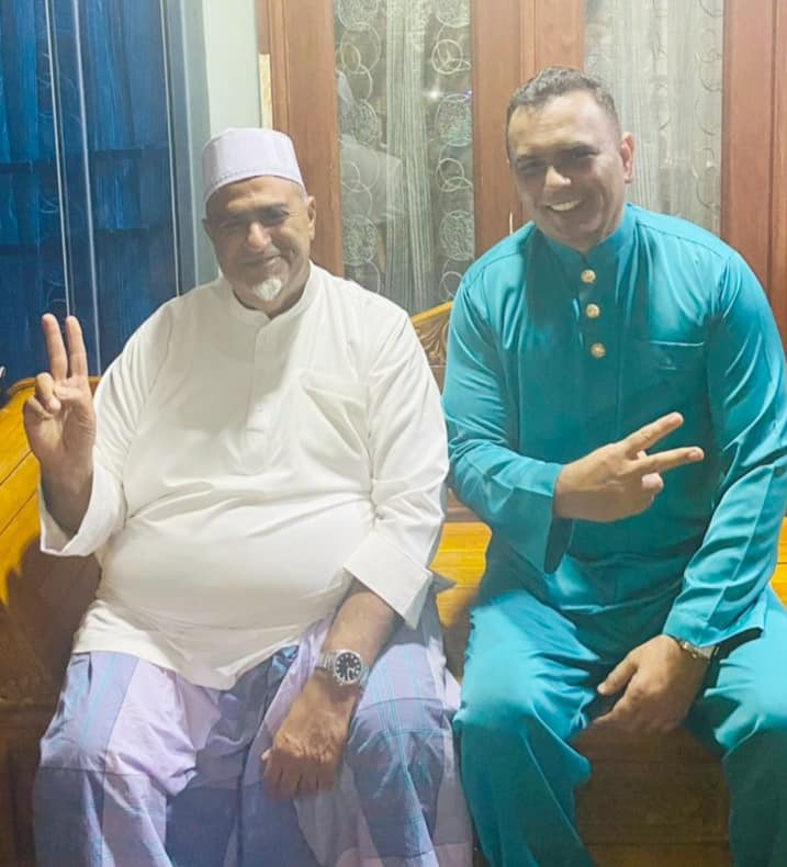 Abdul Salim Abdul Ghani with his friend Amin Ali Sidek. Both smile and show the peace sign. They are in baju melayu. Abdul Salim wears a white kopiah and a sarong. He has a white goatee.