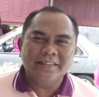Zainee Mohd Zain is smiling. He has thinning hair, bushy eye brows and a round, friendly face.  He is wearing a collared T-shirt.