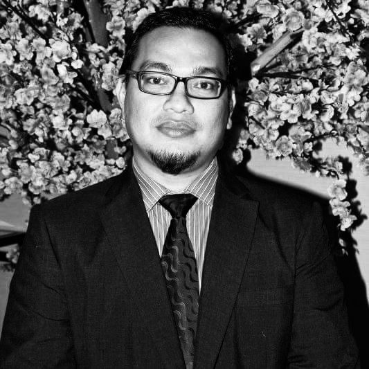 Mohd Hafeiz Bin Mahat poses in front of a floral backdrop. He is wearing a suit and tie. He has dark-rimmed glasses and a goatee.